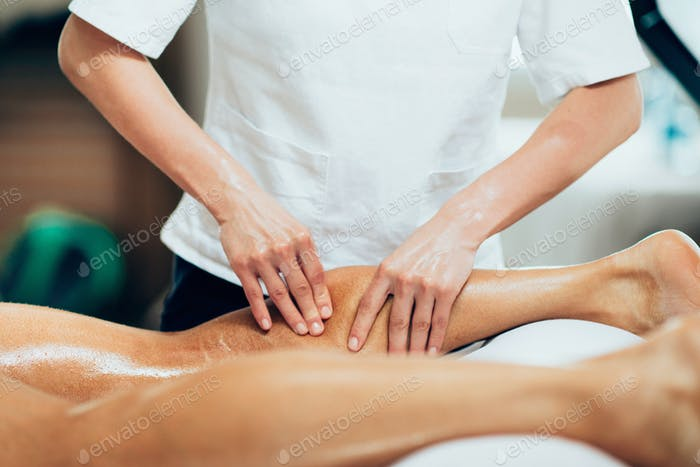 Sports massage. Physical therapyst massaging leg of young male a