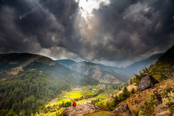 Mountain Valley with sunbeams in cloudy sky