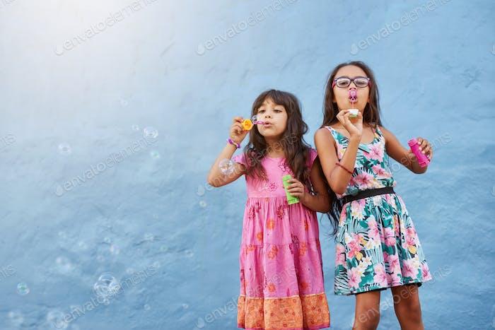Adorable little girls blowing soap bubbles