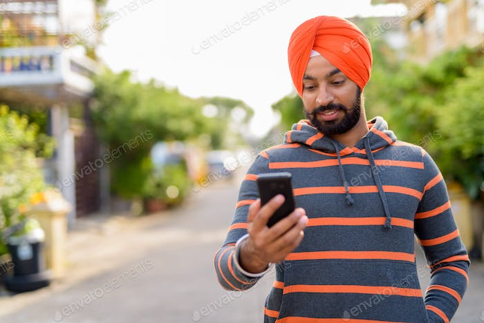 Indian Sikh man wearing using mobile phone outdoors