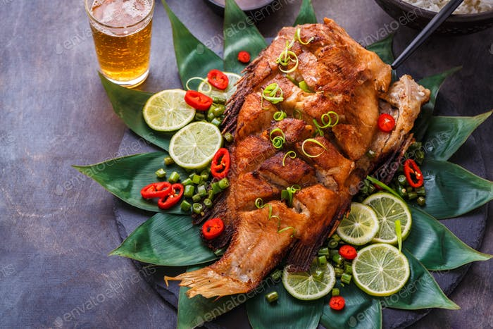 Deep fried whole fish with spicy sauce and coconut rice, thai cuisine