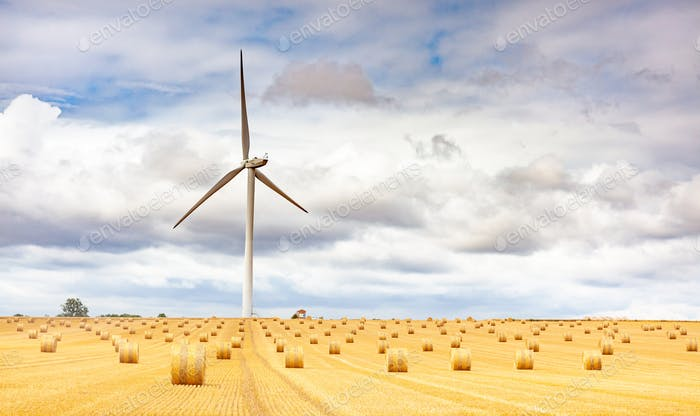 Windmill turbine in a agricultural landscape with fields and meadows. France, Europe.