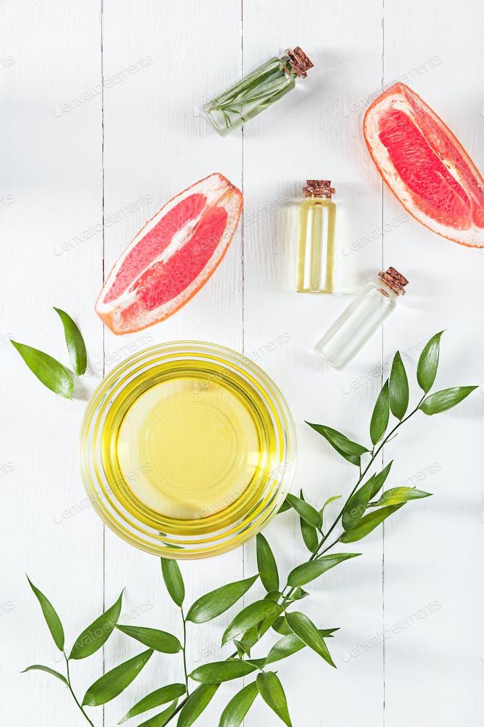 Ätherisches Öl in Glasflasche mit frischer, saftiger Grapefruit und grüner Blätter- Schönheitsbehandlung.