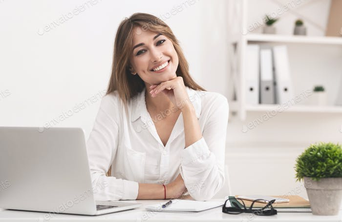 Smiling Businesswoman Sitting At Laptop Posing At Workplace