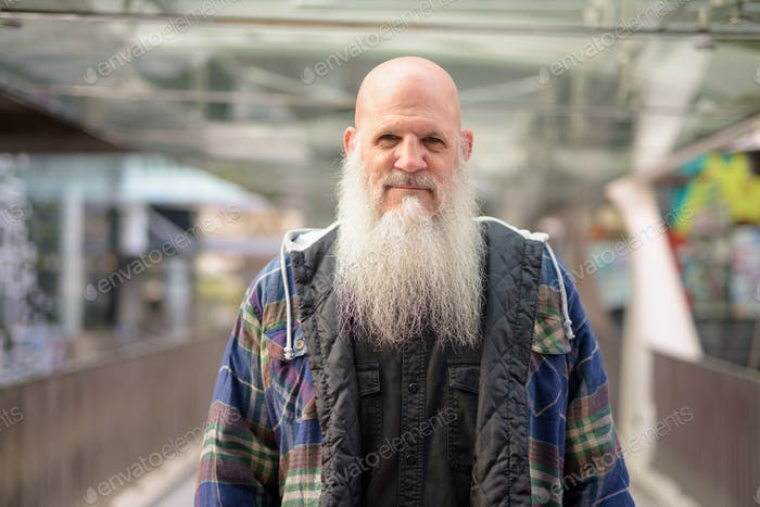 Mature handsome bald hipster man with long beard at footbridge in the city