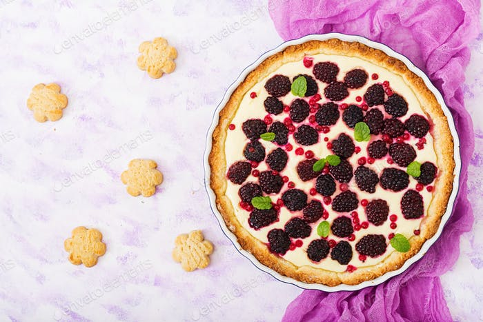 Tart with blackberry and cheesecake cream decorated with mint leaves. Top view. Flat lay