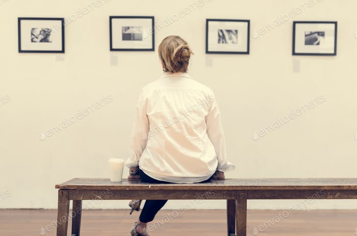 Woman looking at frames in an exhibition