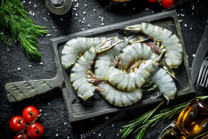 Fresh whole uncooked shrimps with rosemary and tomatoes.