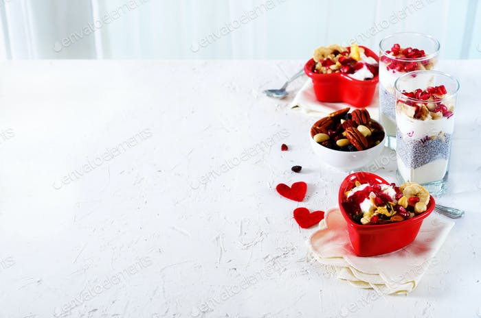 Healthy breakfast - pomegranate, yogurt, granola parfait on white concrete background. Romantic time