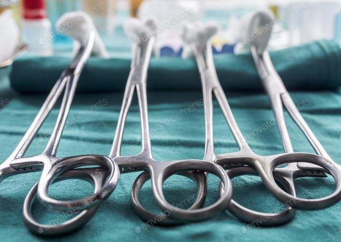 Schere chirurgisch mit Torundas auf einem Tablett Metall in einem Operationssaal, konzeptionelles Bild