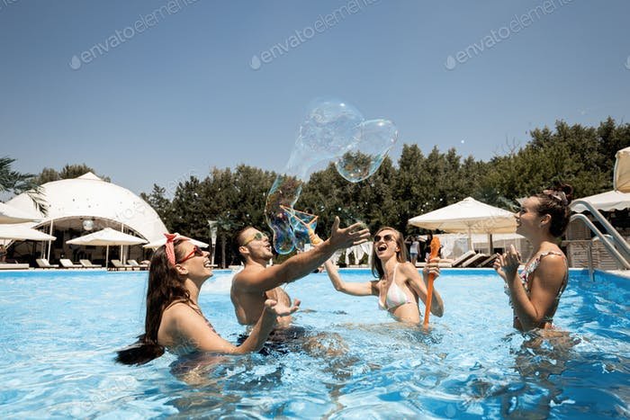 Company of young merry girls and guy are having fun in the swimming pool inflate huge soap bubbles