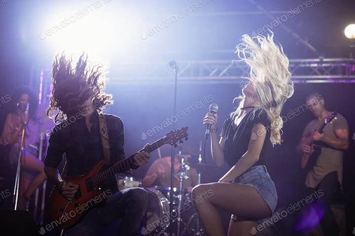 Female singer and male guitarist with tousled hair performing at nightclub