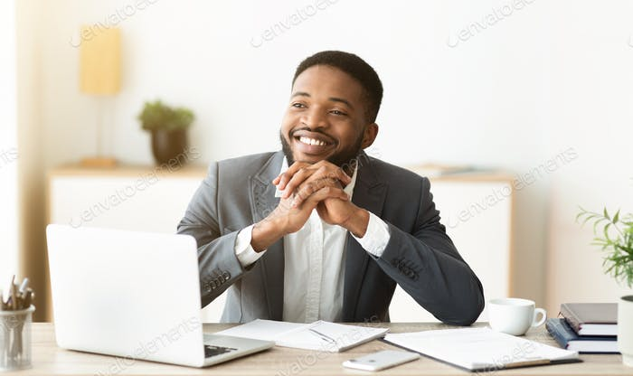 Dreamy black businessman satisfied by results of his company