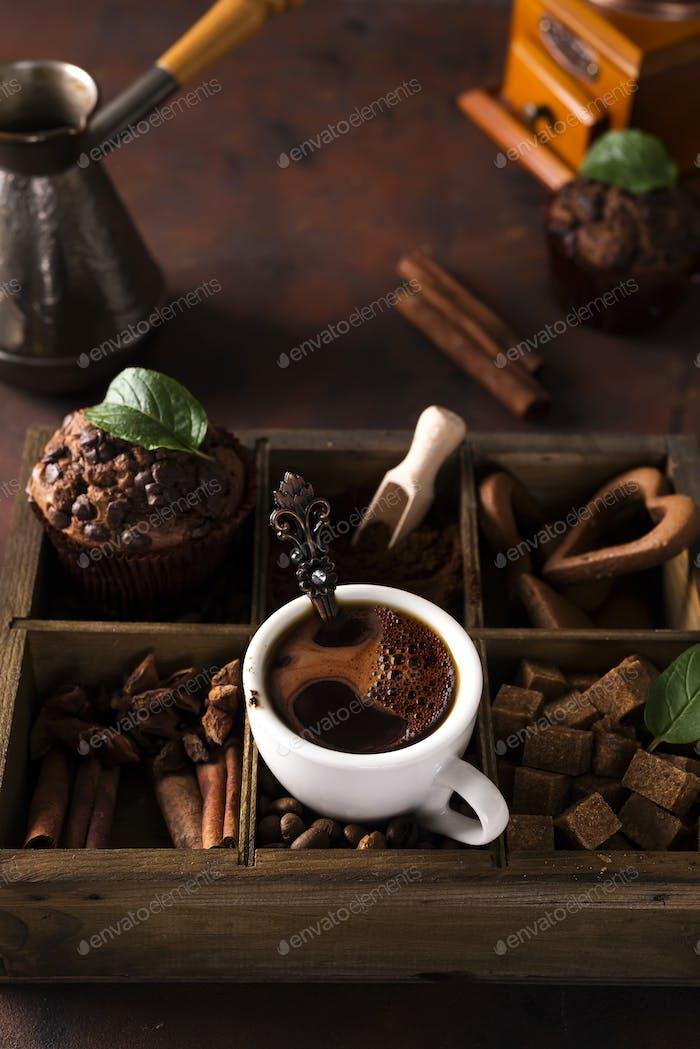 Schokoladenmuffins mit Tasse Kaffee auf einer Holzkiste mit Kaffeekörnern und Gewürzen