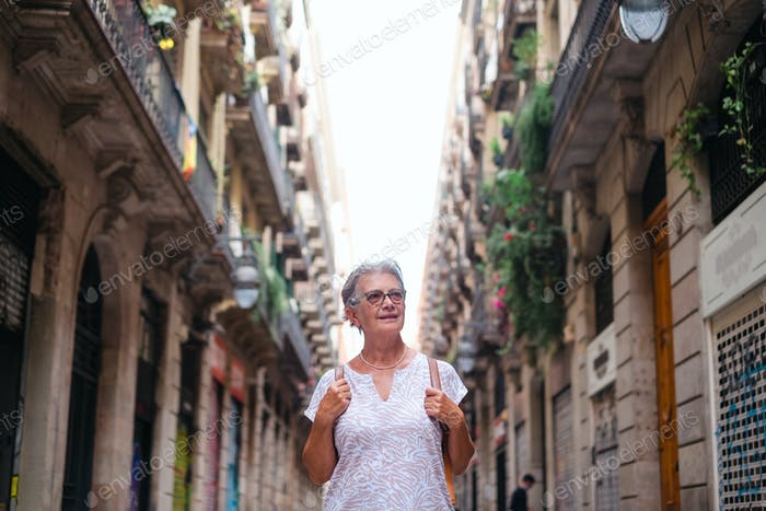 Elderly woman travels to Barcelona visiting the old city part enjoying the holidays