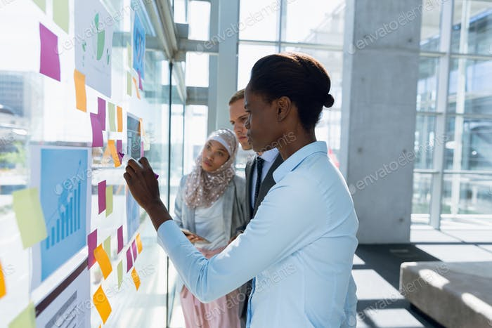 Business people discussing over sticky notes in office