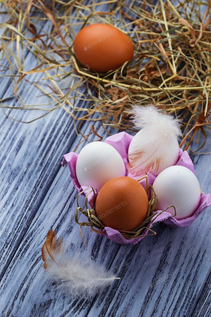 Braune und weiße Eier auf Holzhintergrund