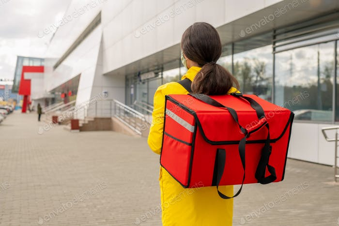 Rear view of young female courier carrying big red bag with orders of clients