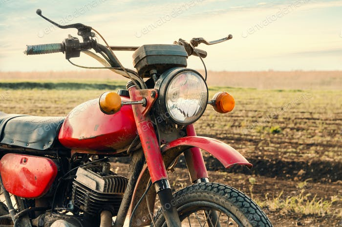 Classic old motorcycle on a dirt road.