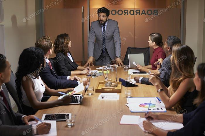 Бизнесмен обращается к коллегам на заседании совета директоров