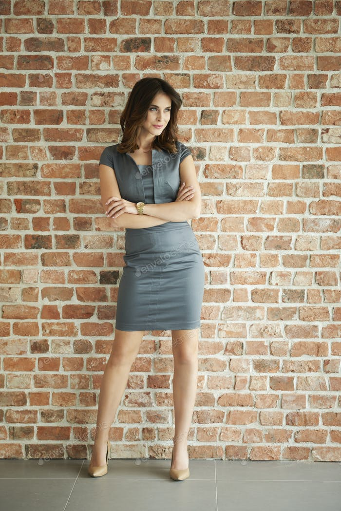 Elegante Frau an der Ziegelmauer