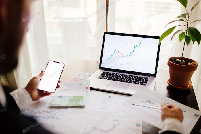 Bróker de inversión que negocia moneda criptográfica bitcoin usando teléfono y computadora portátil