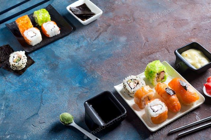Traditionelle japanische Lebensmittel- Sushi, Brötchen, Essstäbchen, Sojasauce auf Farbe Stein Hintergrund. Sushi-Menü