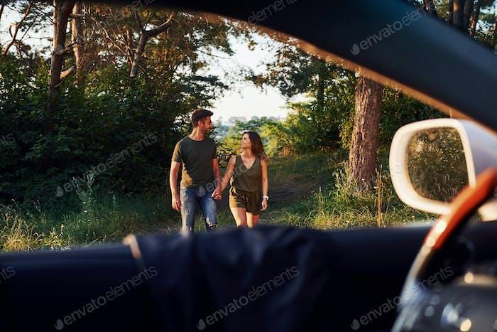Lenkrad, Seitenspiegel Schönes junges Paar haben eine gute Zeit im Wald am Tag