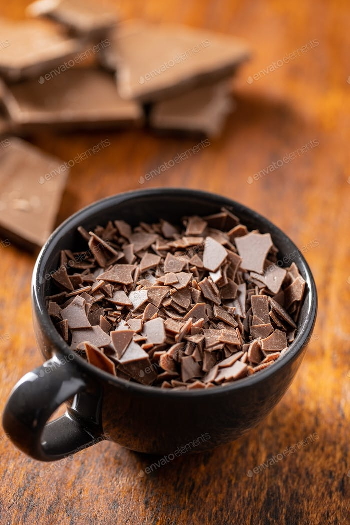 Grated dark chocolate. Chocolate flakes in cup.