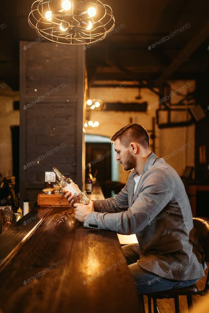 Hombre con botella de alcohol en De madera bar counte