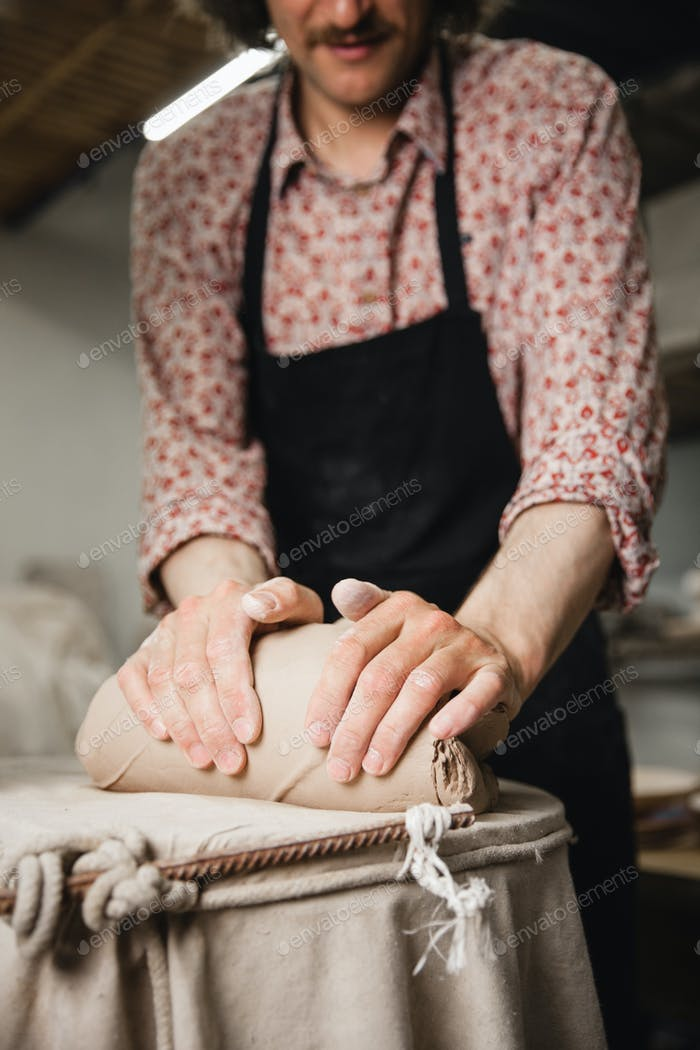 Unrecognizable potter master mashing the clay
