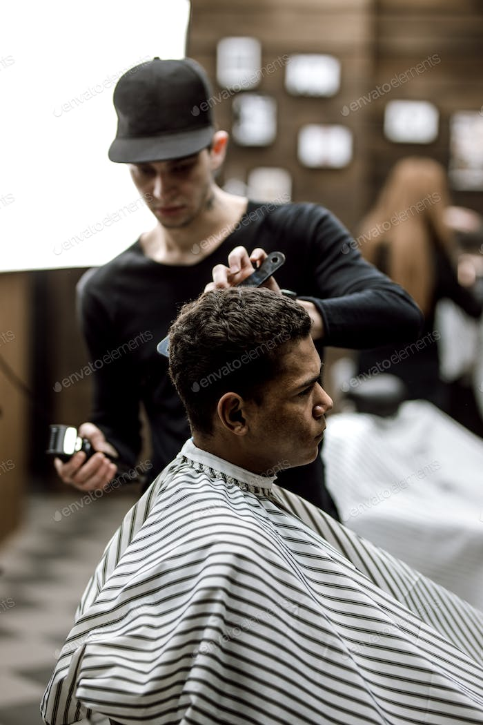 The barber dressed in black clothes makes a razor cut hair back and sides for a stylish man sitting