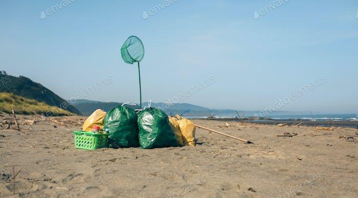 Müllsäcke und Utensilien am Strand