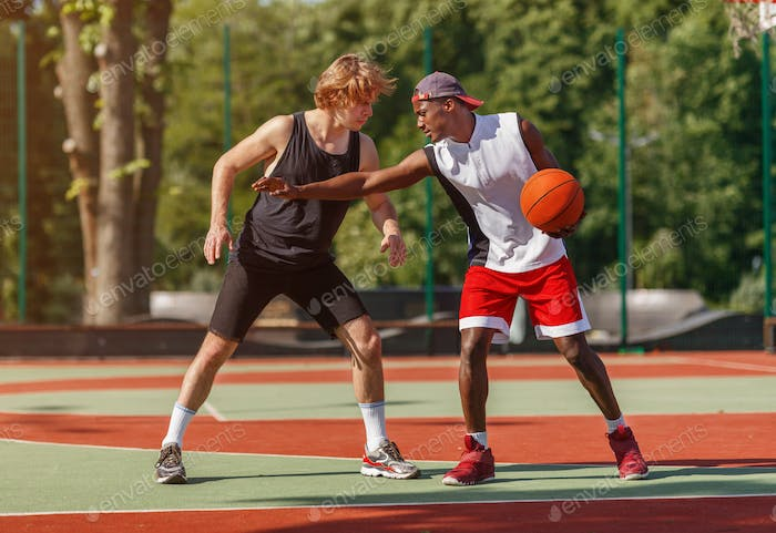 Professional basketball players on outdoor court during friendly game