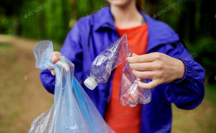 Midsection of young woman picking up litter in nature, a plogging concept