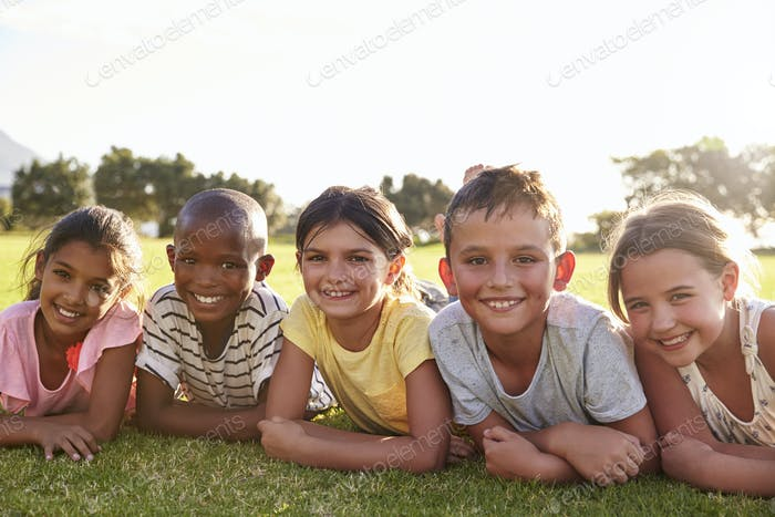 Boys and girls lying on grass in Summer, looking to camera