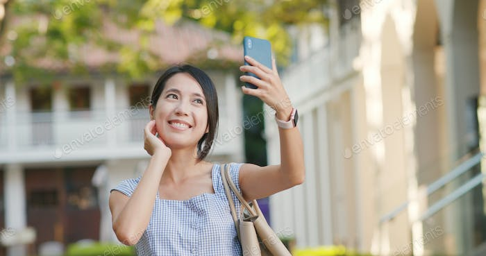 Woman take selfie on cellphone at outdoor