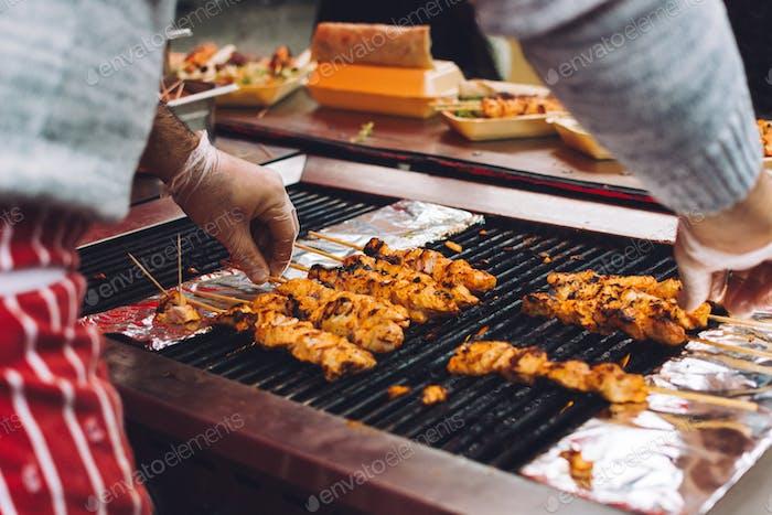 Grilling chicken satay