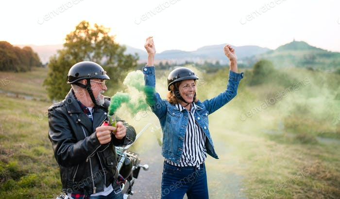 A cheerful senior couple travellers with motorbike in countryside, having fun.
