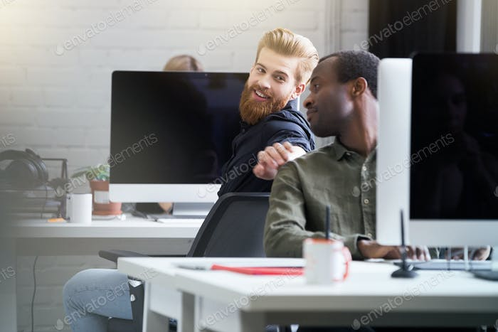 Smiling bearded man getting attention of his male colleague