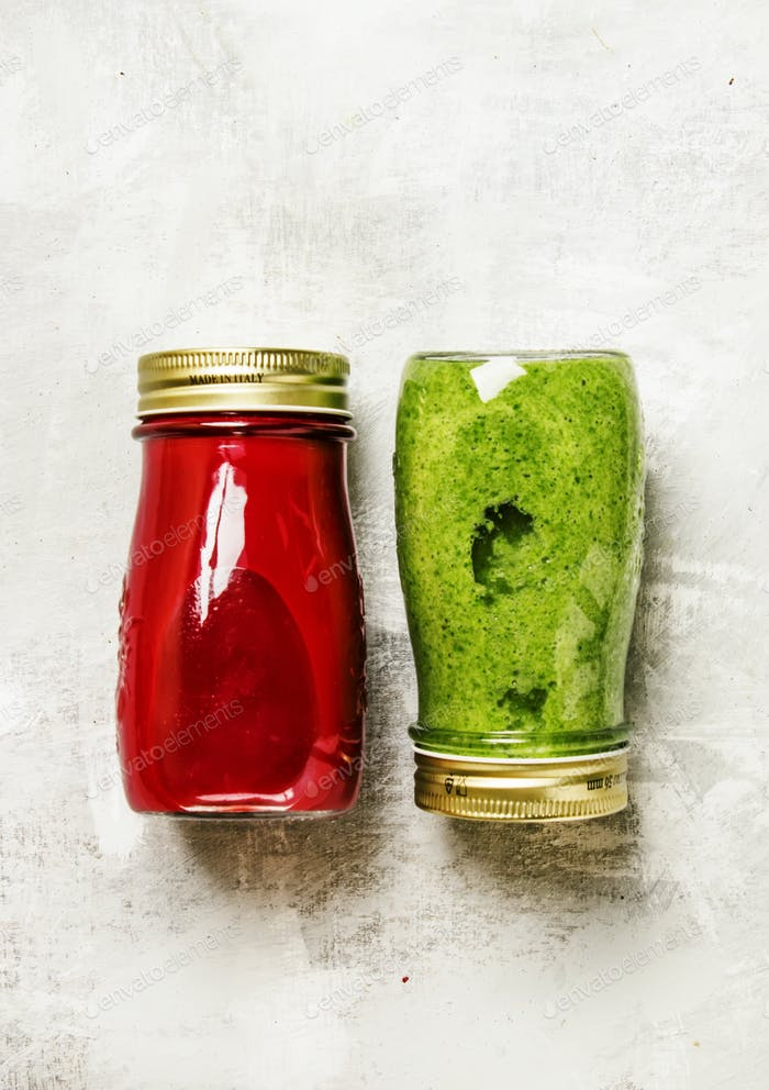 Freshly squeezed spinach smoothie with banana and beets in glass bottles