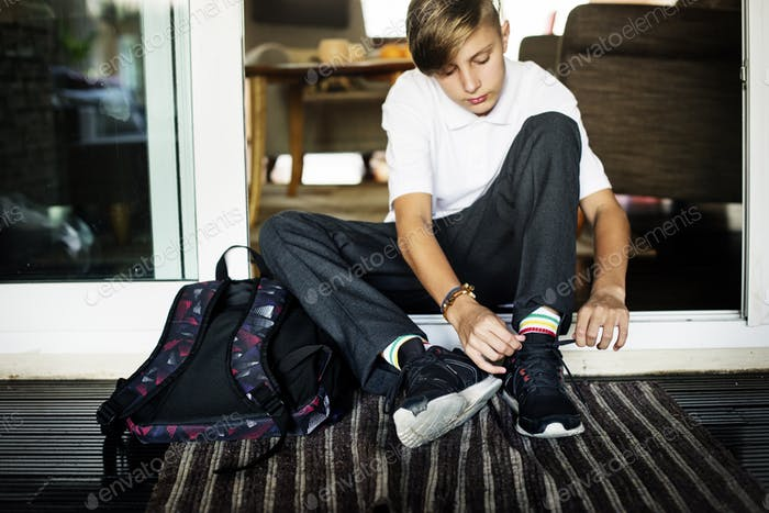 Young caucasian boy sitting on the house entrance tying sneaker