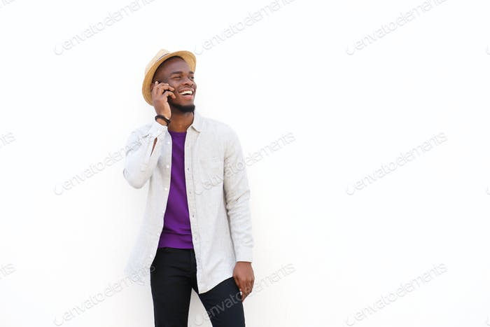 Cheerful young african guy talking on cell phone