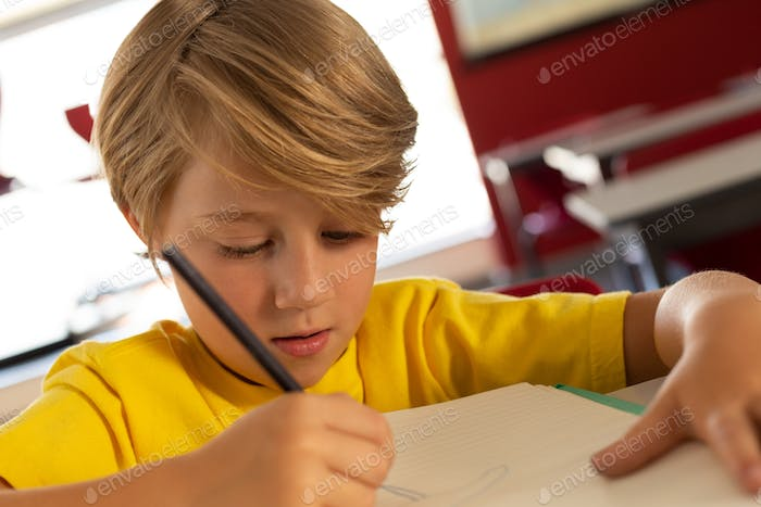 Front view of Caucasian boy drawing sketch on book at desk in a classroom at elementary school