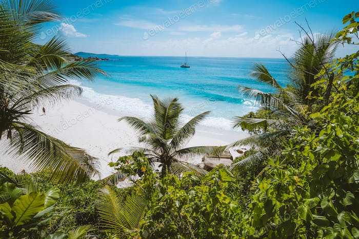 Holiday vacation at Petite Anse paradise beach framed by green foliage. La Digue island, Seychelles