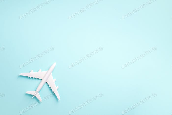 White plane, airplane on blue pastel color background with copy space. Top view, flat lay. Minimal