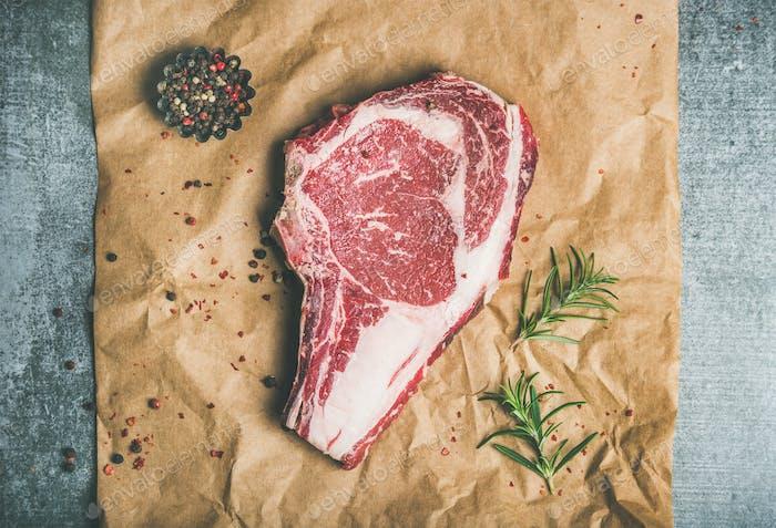 Raw beef steak rib-eye with seasoning on craft paper