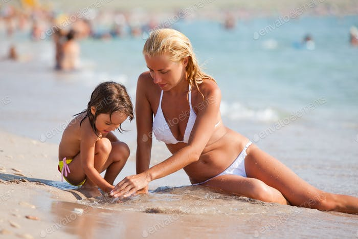 Young mother and her small daughter sitting on sandy beach and playing