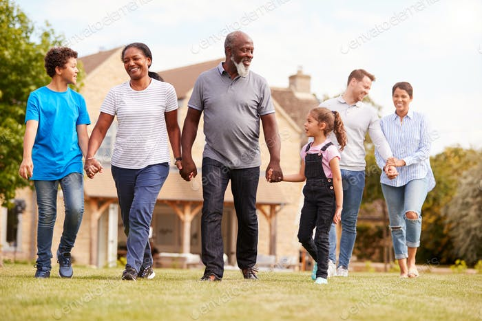 Smiling Multi-Generation Mixed Race Family Walking In Garden At Home