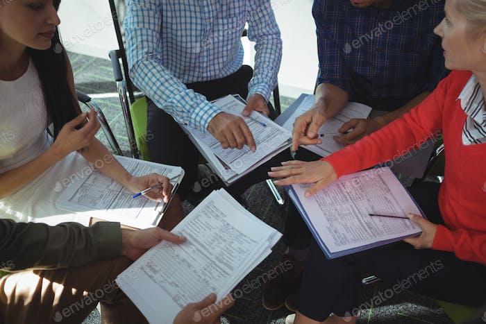 Hohe Ansicht von Geschäftsleuten, die zusammen mit Dokumenten sitzen